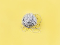 Hank ball of gray knitting wool yarn on illuminated yellow backdrop