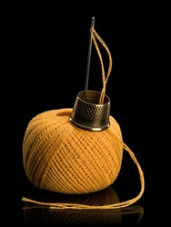 Hank of yellow threads for darning, needle and brass thimble it is isolated on black