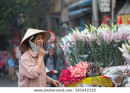 Hanoi, Vietnam, Apr 5, 2014:Life in Vietnam-  A woman selling flowers on the streets of Hanoi. Flowers are selling all the time in Hanoi, special when Tet and holidays