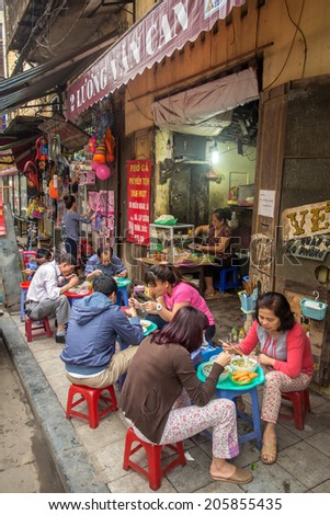 HANOI, VIETNAM - APRIL 8, 2014: Customers have their meal on the street stall on April 8, 2014 on Hanoi. Vietnamese people love to socialise as they eat.