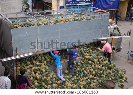 Hanoi Vietnam April 6 2014 Stevedores unloading pineapples from trucks to deliver to fruit stores