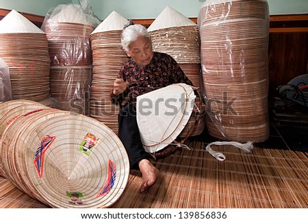 HANOI, VIETNAM - APRIL 21: Vietnamese woman sitting sewing hats in a traditional village in Vietnam April 21,2013. Conical hat is an traditional item of ethnic Vietnam