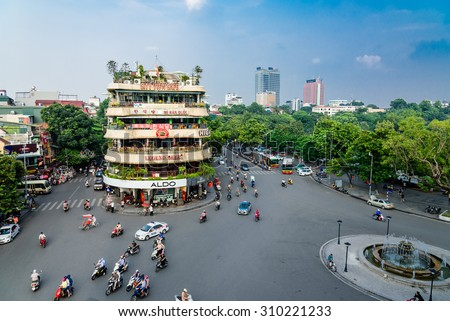 HANOI, VIETNAM - AUG 26,2015: Vehicles running on a busy street near Hoan Kiem lake (Sword lake) in Hanoi capital, Vietnam. This area is located in the old quarter, the center of Hanoi