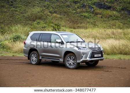 Hanoi, Vietnam - Dec4, 2015: Lexus LX 570 2016 car running on the mountain road in the rain in Vietnam. Lexus LX 570 is a luxury SUV with great off-road capabilities. #348077477