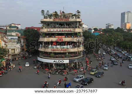 HANOI, VIETNAM - DEC 13, 2014: Vehicles running on a busy street near Hoan Kiem lake (Sword lake) in Hanoi capital, Vietnam. This area is the center of Hanoi.
