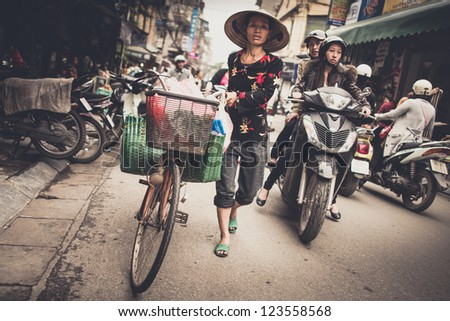 HANOI, VIETNAM - DECEMBER 01: An unidentified woman in busy Hanoi traffic on December 01, 2012 in Hanoi, Vietnam