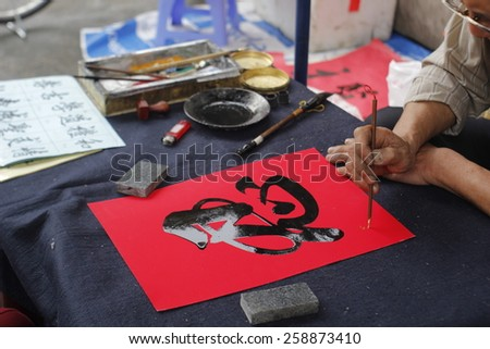 Hanoi, Vietnam - Feb 19, 2015 Calligrapher writing words on paper. Calligraphy is old culture of Vietnam