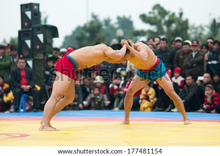 HANOI, VIETNAM, FEBRUARY 16: Two wrestlers in a match in traditional wrestling championship on February 16, 2014 in Hanoi, Vietnam. Wrestling is a traditional sport in Vietnam