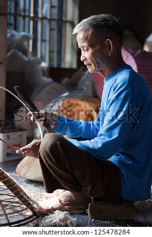 HANOI, VIETNAM - OCTOBER 23: Vietnamese man sitting sewing hats in a traditional village in Vietnam October 23, 2010. Conical hat is an traditional item of ethnic Vietnam