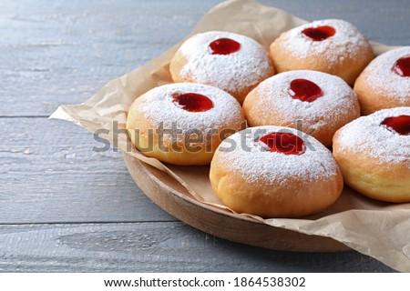 Hanukkah doughnuts with jelly and sugar powder on grey wooden table, closeup ストックフォト ©