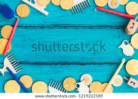 Hanukkah dreidels with Menorah and some Hanukkah coins and Hanukkah candles on a vintage wood background. Overhead or top view composition with copy space. Translation: Happy Holyday, G,G,N #1219222189