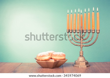 Hanukkah menorah with burning candles and donuts. Retro old style filtered photo #345974069
