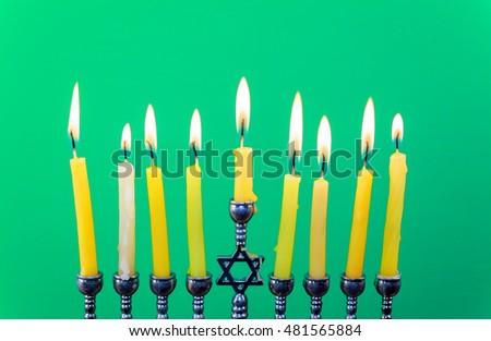 Hanukkah menorah with candles Hanukkah candles happy burning green background isolation #481565884