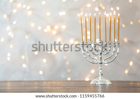 Hanukkah menorah with candles on table against blurred lights #1159455766