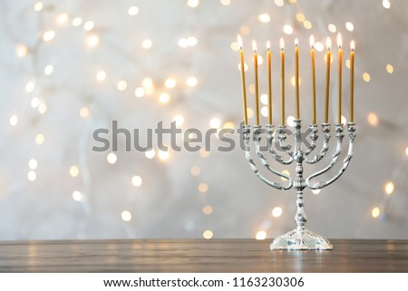 Hanukkah menorah with candles on table against blurred lights #1163230306