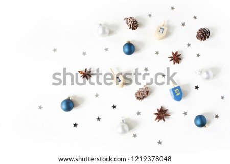 Hanukkah styled stock composition. Decorative pattern. Wooden dreidel toys, larch cones, anise and silver confetti stars decoration on white background. Flat lay, top view. Jewish design.