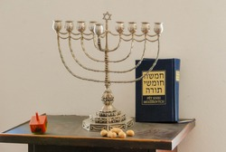 Hanukkiot (candle holder), dreidl (jewish wood top) and the book of Torah for the jewish holiday of Hanukkah. Translation of the title of the book: