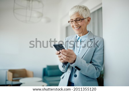 Hap mature businesswoman using smart phone and reading text message in the office. Stok fotoğraf ©