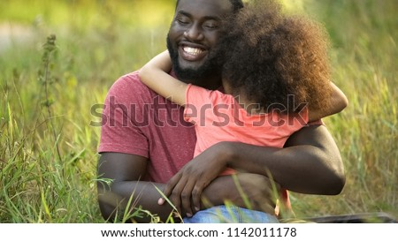 Happiest father on Earth embracing cherished daughter in tight and tender hug