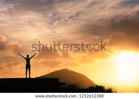 Happiness- achievement- feeling adventurous. Young female with hands raised standing high up on a mountain