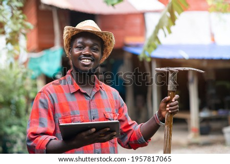 Happiness african male farmer stands and using tablet with his farmhouse in the background Photo stock ©