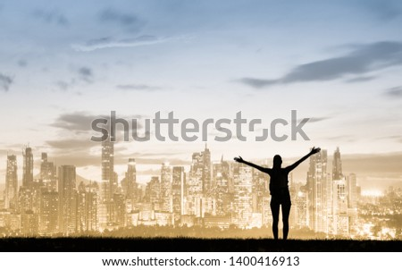 Happiness and freedom in the big city. Young woman with arms in the air facing city skyline.  #1400416913