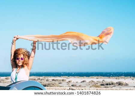 Happiness and freedom joy people concept with attractive middle age traveler out of a convertible car smiling and enjoying playing ith the wind in holiday vacation with blue sea and sky in background