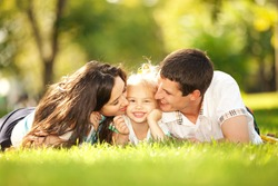 Happiness and harmony in family life. Happy family concept. Young mother and father kissing their daughter in the park. Happy family resting together on the green grass. Family having fun outdoor