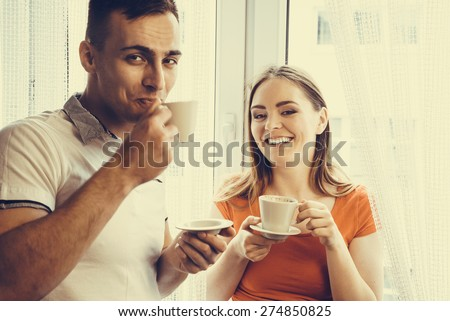 Happiness and healthy relationship concept. Attractive couple drinking tea or coffee together at home, man and woman holding cups with hot beverage at home