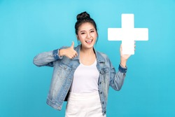Happiness asian woman smiling, showing plus or add sign and thumb up or like on blue background. Cute asia girl wearing casual jeans shirt and showing join sign for increse and more benefit concept