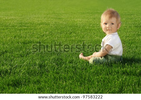 Happiness Baby boy sitting on the grass in field