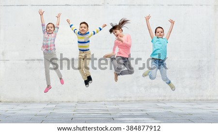 happiness, childhood, freedom, movement and people concept - happy little girl jumping in air over concrete wall on street background