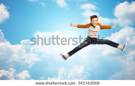 happiness, childhood, freedom, movement and people concept - happy smiling boy jumping in air over blue sky and clouds background #341562068