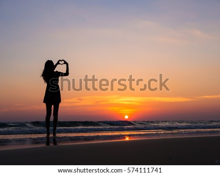 happiness concept, silhouette of woman showing love, making heart shaped gestures with hands and enjoying sunset at beach #574111741