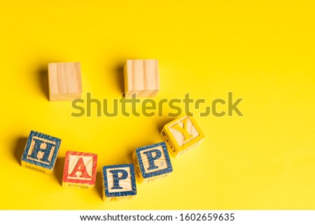 Happiness concept: wooden blocks forming a smiling face against yellow background.  Copy space for text stock photo