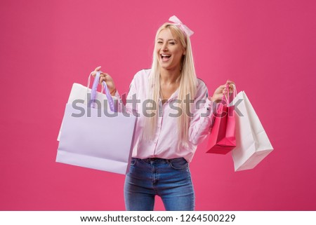 Happiness, consumerism, sale and people concept - smiling shocked young blond woman with shopping bags over pink background
