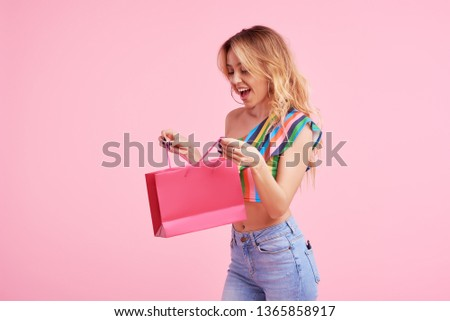 happiness, consumerism, sale and people concept - smiling young woman with shopping bags over pink  background