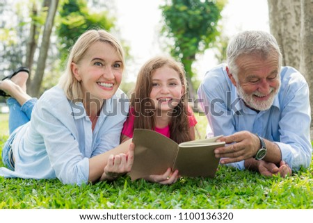 happiness family elderly caucasian and child caucasian with book activity relax on lawn in weekend holiday lifestyle park outdoor nature background. #1100136320