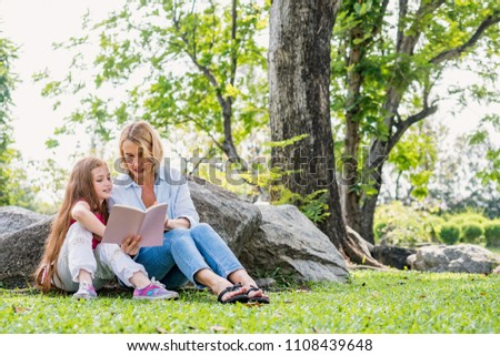 happiness family elderly caucasian woman and caucasian child read book relax in park outdoor nature background. #1108439648
