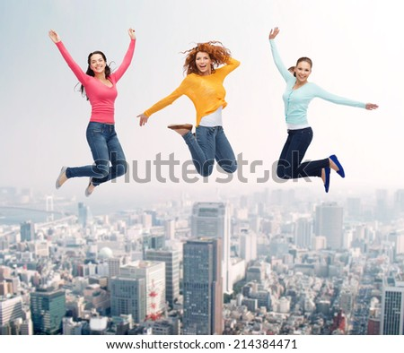 happiness, freedom, friendship, movement and people concept - group of smiling young women  jumping in air over city background