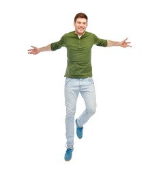 happiness, freedom, motion and people concept - smiling young man jumping in air