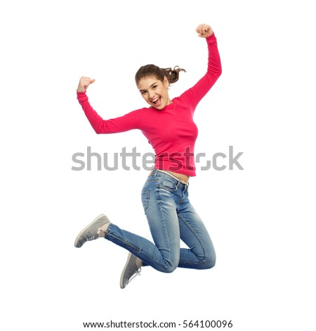 happiness, freedom, power, motion and people concept - smiling young woman jumping in air with raised fists over white background