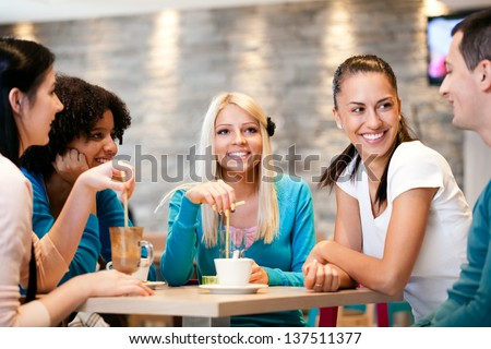 Happiness friends enjoying coffee together in modern  cafe