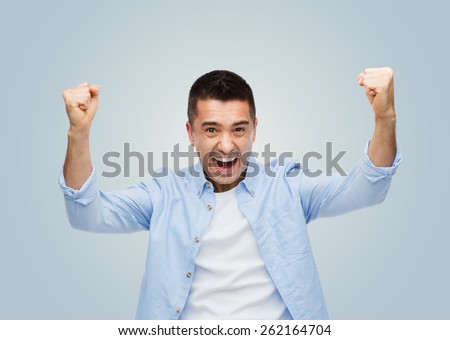 happiness, gesture, emotions, joy and people concept - happy laughing man with raised hands over gray background