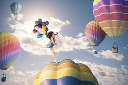 Happiness girl jumping over hot air balloon