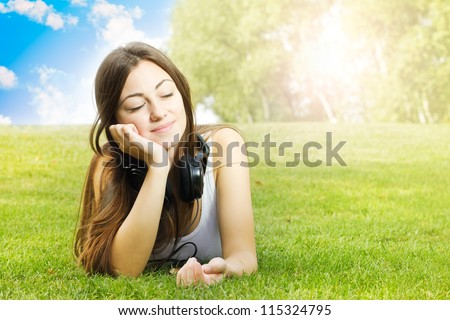 Happiness girl with headphones enjoying nature at sunny day.