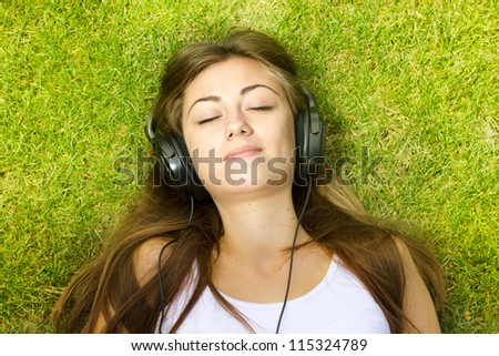 Happiness girl with headphones relaxing on green grass in the park.