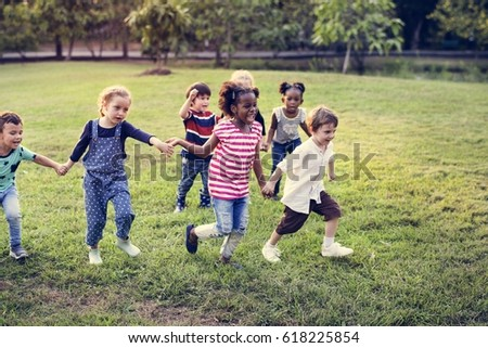 Happiness group of cute and adorable children playing in the park #618225854