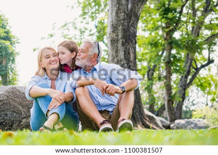 happiness harmony family elderly caucasian and child caucasian kissing their in the park ,love people resting together on the green grass ,Happy family concept.  #1100381507