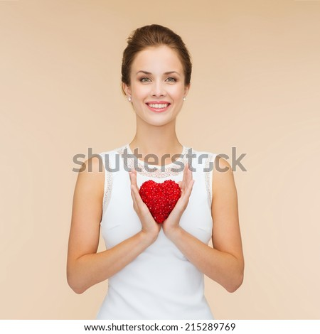happiness health charity and love concept smiling woman in white dress with red heart over beige background